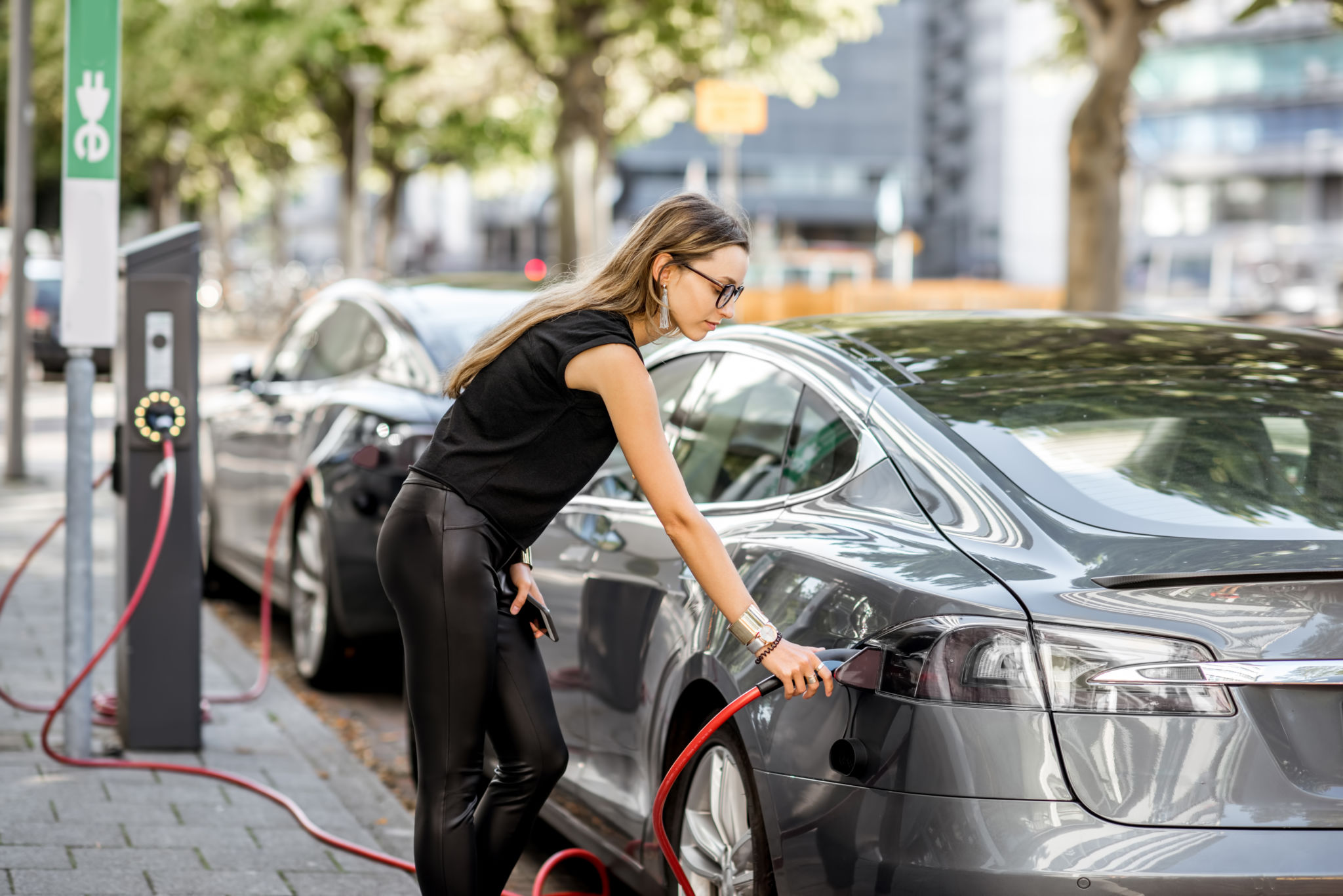 Woman charing electric cars connected to power grid